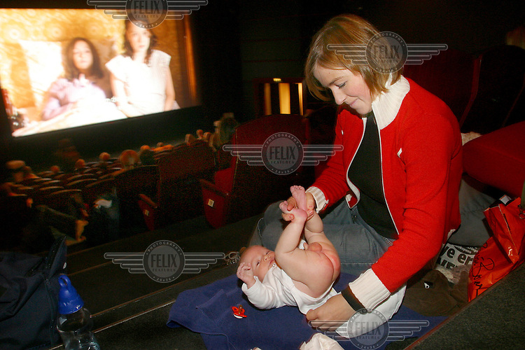 """A young mother changes her son's nappy in the cinema. In specially organised """"baby-movie"""" showings popular films are screened with lower volume and with space made available for pram parking..In contrast to most European countries, the Norwegian birth rate is a healthy 1.9. Norway's reputation as a child friendly society is partially founded on a succession of government initiatives to improve parents' rights and economic circumstances."""