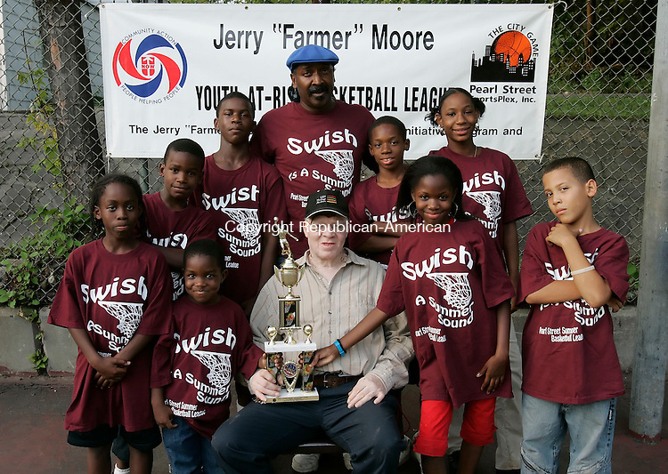 WATERBURY,  CT 19 September 2005 -091905BZ06- Front row from left- Shaquille Robinson, 11; Donte Jordan, 4; Jerry &quot;Farmer&quot; Moore; April Robinson, 12; Brandon Espinal, 8.<br /> Back row from left- Dayshawn Smith, 11; Kenny Smith, 13; Coach James Hill; Shawn Walton, 12; and Latoya Kimbrough, 14.<br /> Champions in the Jerry &quot;Farmer&quot; Moore Youth At Risk Basketball League pose for a photo on the basketball court at Martin Luther King Jr. park Monday afternoon.<br /> Monday afternoon.<br /> Jamison C. Bazinet / Republican-American