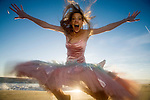 Happy girl jumps for joy at the beach, Los Angeles, California, USA, America, at dusk