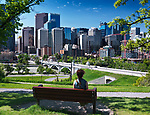 Young woman sitting alone on a bench in Sunnyside Bank Park on a sunny summer day with Centre Street Bridge and Calgary city downtown beautiful skyline view in the background. Calgary, Alberta, Canada 2017.