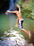 USA, Hawaii, Oahu, a boy jumps off of a rock and into the water at Sacred Falls