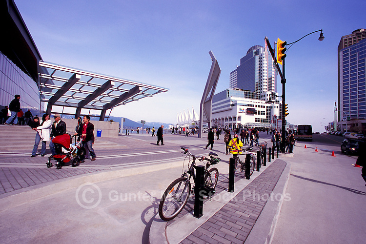 "Tourists walking along Plaza at the Entrance to the New Convention and Exhibition Centre Vancouver, British Columbia, Canada.  ""Canada Place"" in Background."