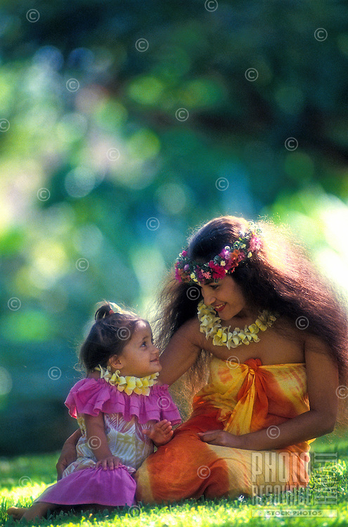 A beautiful Polynesian woman with her daughter, both dressed in colorful Hawaiian clothes and wearing plumeria leis, sit on the grass talking.