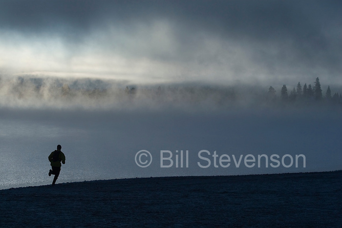 A picture of a man running along the shore of a misty lake at dawn near Truckee California