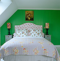 In the bedroom a floral theme runs through from the antique 19th century quilt and the chintz headboard to the bedside lamps