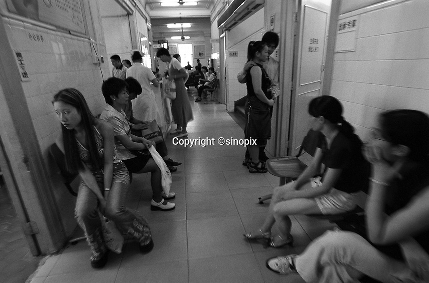 Women wait outside an abortion ward in a Hospital in Guangdong. Guangdong province has a high abortion rate partly due to many females travelling from Hong Kong. Official of Guangdong are penalised financially if they do not reach their abortion quota.<br /> 2002<br /> <br /> photo by Richard Jones / Sinopix