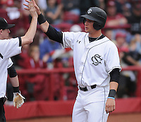 First baseman Kyle Martin (33) of the South Carolina Gamecocks is congratulated after scoring a run in a game against the Clemson Tigers on March 3, 2012, at Carolina Stadium in Columbia, South Carolina. South Carolina won, 9-6. (Tom Priddy/Four Seam Images)