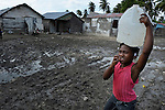A girl carries water in Batey Bombita, a community in the southwest of the Dominican Republic whose population is composed of Haitian immigrants and their descendents.