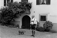 Italy. South Tyrol. Tisens. A bald elderly man, dressed with Lederhosen, is waiting with his dog for the start of the religious procession on August 15 for the Assumption. Lederhosen are breeches made of leather; they may be either short or knee-length. The Assumption of the Virgin Mary into Heaven, often shortened to the Assumption, is also known as the Falling Asleep of the Blessed Virgin Mary, According to the beliefs of the Catholic Church was the bodily taking up of the Virgin Mary into Heaven at the end of her earthly life. The Assumption is a major feast day, commonly celebrated on August 15th. The feast is marked as a Holy Day of Obligation in the Roman Catholic Church. South Tyrol (German: Südtirol; Italian: Sudtirolo, also known by its alternative Italian name Alto Adige) is an autonomous province in northern Italy. 15.08.1999 © 1999 Didier Ruef
