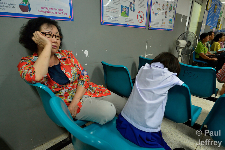 United Methodist missionary Cindy Moon waits with 9-year old Play Nata to see a dentist in Chiang Mai, Thailand. The girl is an HIV positive orphan, one of eight such girls that lives in an orphanage directed by Moon and her husband Gary.