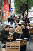 Young people sit outside a cafe in central London.