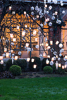 A tree in the garden decorated with glass baubles and tealights creates a magical effect