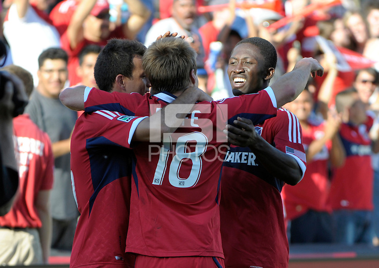 Chicago forward Chris Rolfe (18) is congratulated by Marco Pappa (left) and Patrick Nyarko (right) after scoring Chicago's third goal.  The Chicago Fire defeated the New York Red Bulls 3-1 at Toyota Park in Bridgeview, IL on June 17, 2012.