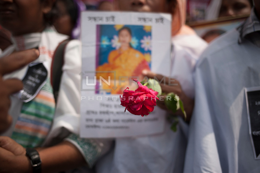 Relative of victims killed in the collapse of Rana Plaza holds flower and the picture of her daughter as she take part in a protest during the second anniversary of the building collapse in Savar, near Dhaka, Bangladesh