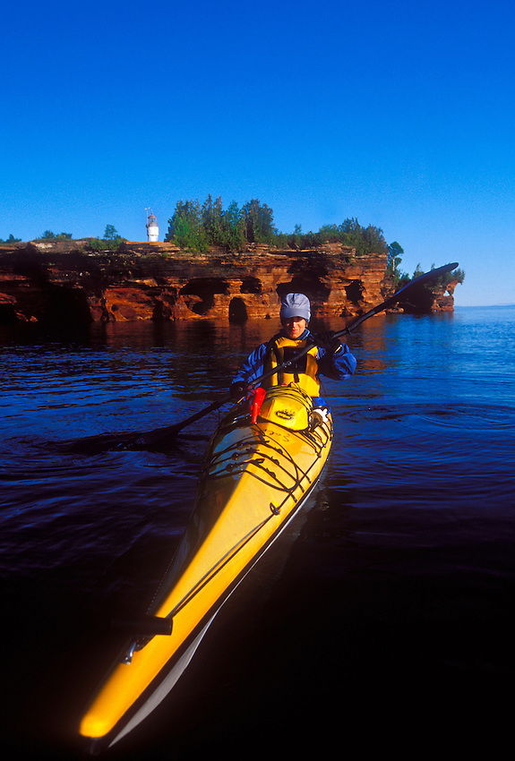A sea kayaker with sea caves and Devils Island Lighthouse on Devils Island in Apostle Islands National Lakeshore near Bayfield, Wis.