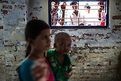 Men peek from the window while a woman and her child wait for their turn at the general OPD of the Duncan Hospital in Raxaul, Bihar, India.