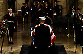 A member of the military stands watch over the flag draped casket of former President George H.W. Bush in the Capitol Rotunda in Washington, DC, December 3, 2018. - The body of the late former President George H.W. Bush will travel from Houston to Washington, where he will lie in state at the US Capitol through Wednesday morning. Bush, who died on November 30, will return to Houston for his funeral on Thursday. (Photo by Brendan SMIALOWSKI / POOL / AFP)