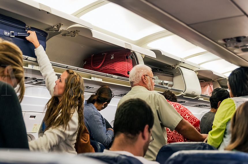 Airline travelers retieve their carry-on luggage from overhead compartments.