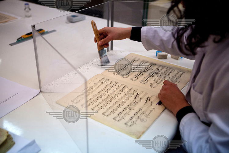Staff working, in the preservation laboratory, on some recently discovered Tchaikovsky sheet music used by the Auschwitz prisoner's orchestra. The Museum Preservation Department is responsible for protecting everything that remains at the Auschwitz-Birkenau Concentration Camp site. It is estimated that between 1.1 and 1.5 million Jews, Poles, Roma and others were killed in Auschwitz-Birkenau during the Holocaust between 1940-1945. 27 January 2015 is the 70th anniversary of the liberation of Auschwitz-Birkenau.