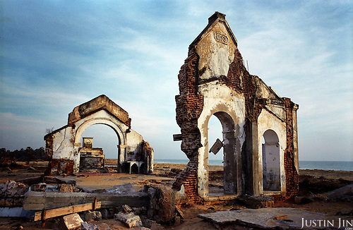 A church ravaged by the tsunami stands on the beach in the northeastern coast of Sri Lanka, an area torn also by civil war. .The December 26, 2004 tsunami killed around 40,000 people along Sri Lanka's southern, eastern and northern shores, tearing thousands of families apart. .The bulk of the dead were women and children - husbands lost young brides and around 4,000 children lost one or both parents. .Even before the tsunami struck, people here in the northeast had already been displaced four times by the Tigers' two-decade war for autonomy. .In some places, the scars of war and the tsunami have become one. Remnants of walls torn down by waves are pockmarked with bullet holes and shrapnel from shells fired before a 2002 ceasefire plunged a civil war that killed over 64,000 people into limbo. ..Picture taken March 2005 by Justin Jin