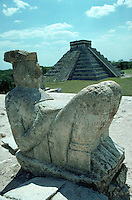 Chac-Mool statue at Temple of Warriors with Castle of Kukuclan in background at Mayan ruins of Chichen Itza. Yucatan, Mexico.