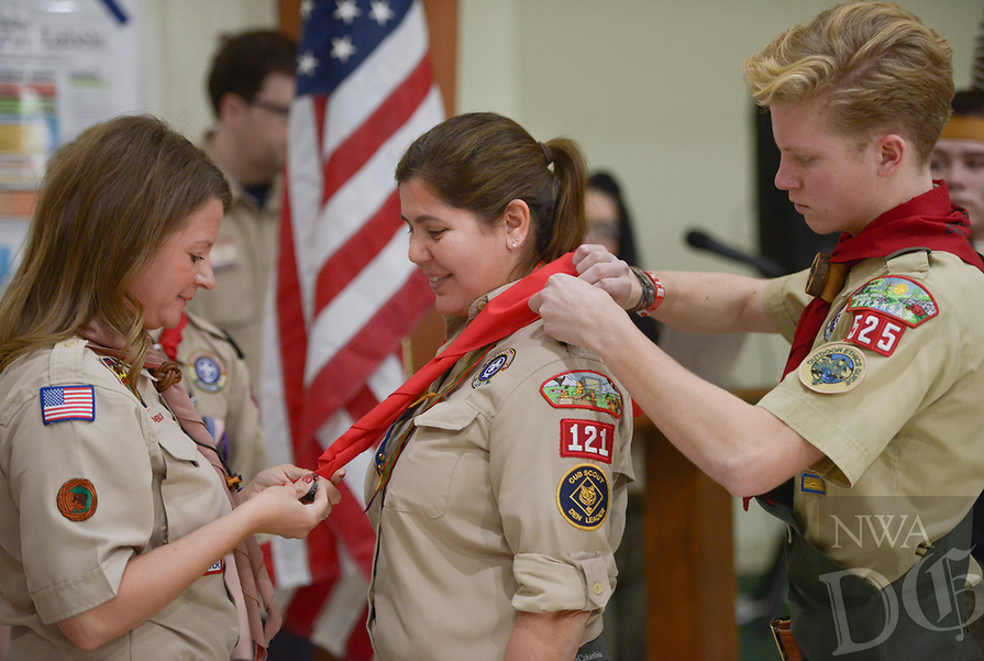 NWA Democrat-Gazette/CHARLIE KAIJO Amanda Tyburski (left) wraps a Scouts neckerchief around Annabella Freeman (center) during her crossover ceremony, Saturday, February 2, 2019 at the First Presbyterian Church in Bentonville. Annabella was a den leader in her daughter's Cub Scout pack before becoming an assistant scoutmaster in troop 525 of the new Scouts BSA program.