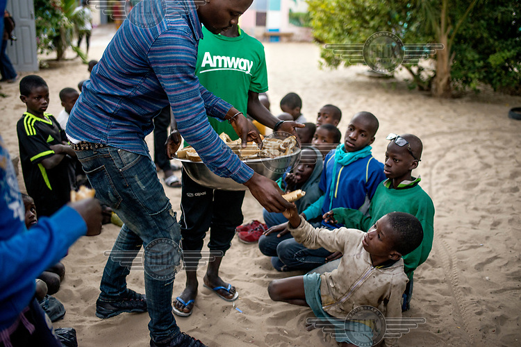 Abdourahmane Soumare, a teacher, hands out sandwiches to the ever hungry ex-Talibe at the Maison de la Gare, a charity that seeks to rehabilitate Talibe (children who live and study the Koran at a Daara, religious school). <br /> Talibe often have issues that stem from being separated from their parents at a young age and the abuse they endure at the Daaras where they are expected to beg to raise money for the Daara's marabout and to get food to fed themselves.