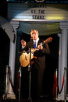 George Bush impersonator sings and plays a guitar