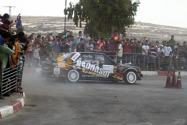 Palestinians watch a car race organized by the Palestinian Federation of Cars and Motorcycles Sports in the West Bank town of Ramallah, on 20 September 2013. Photo by Issam Rimawi