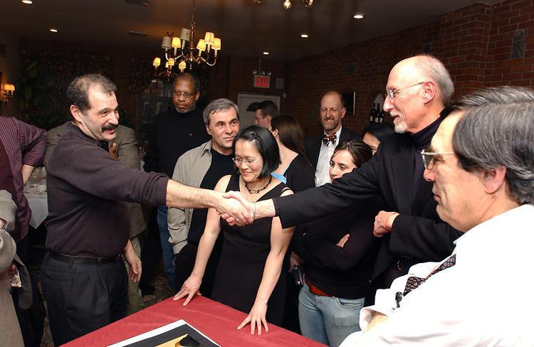 Bruce Gilbert shakes hand of Jim Dooley surrounded by Newsday Photo Dept. staff during the presentation of an album of the staff's favorite photos at retirement dinner for Dooley held at the Manducatis Restaurant in long Island City on Wednesday February 9, 2005. (Photo copyright Jim Peppler 2005).
