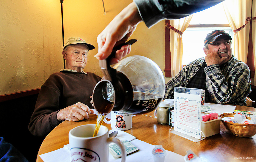 "Warren, NH,  Wednesday, June 3, 2015:  Coffee cups are topped off as Lyle Moody, left, and Dana Leonard, right, look on at Calamity Jane's Restaurant.  The so-called ""men's coffee club"" sits at Calamity Jane's Restaurant most mornings, passing time by talking about whatever comes to mind and drinking coffee. Among the group, Lyle Moody, who at 93 is Warren's oldest resident and the town's unofficial historian. Also part of the group is Bob Giuda, the town moderator.  CREDIT: Cheryl Senter for The Boston Globe"