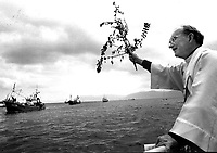 Canon Tomas O'Fiannachta blesses the boats in Dingle Harbour at the annual festival in 1992.<br /> Picture by Don MacMonagle
