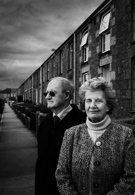 Elisabeth Rickard and her cousin Paul Langford, both descendants of the miner poet John Harris (1820-84), in front of the terraces of mining cottages in Troon, Cornwall.