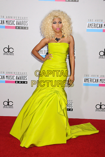 Nicki Minaj.40th Anniversary American Music Awards - Arrivals held at Nokia Theatre L.A. Live, Los Angeles, California, USA..November 18th, 2012.AMA AMAs full length yellow strapless drop waist dress hand on hip necklace .CAP/ADM/BP.©Byron Purvis/AdMedia/Capital Pictures.