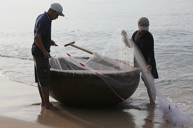 Two men gather a net into a traditional woven bamboo boat in Mui Ne, Vietnam. Nov. 20, 2011.