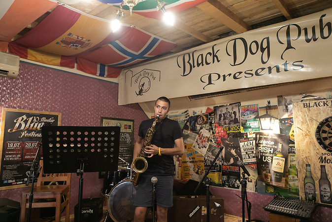 A waiter in pub plays saxophone in old town in Mostar.