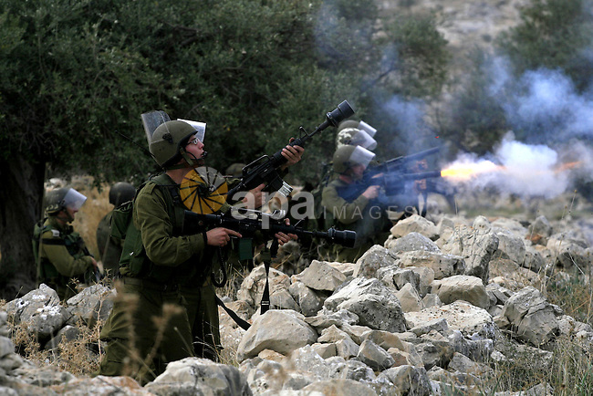 Israeli soldier fire tears gas grenade during a demonstration against Israel's controversial separation barrier in the West Bank village of Nilin, near Ramallah, on Dec 4, 2009. Israel says the projected 723 kilometres (454 miles) of steel and concrete walls, fences and barbed wire are needed for security. Palestinians view it as a land grab that undermines their promised state. Photo by Issam Rimawi