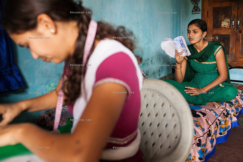 Video Volunteer videojournalist Niru J. Rathod (right), 24, studies law while her sister Mukta (left), 22, sews clothes for customers at home in Surendranagar, Gujarat, India on 14 December 2012. While Niru's sisters have become seamstresses or housewives, Niru, the 8th child in a family of 11 girls born to a Dalit construction worker, has been using videography for social change since 2006. She shoots and produces her own short documentaries and is a committed video activist, having conducted hundreds of village video screenings where she also speaks to thousands of men, shattering their ideas about what a woman and a Dalit can do while bringing massive changes to the communities she documents. Photo by Suzanne Lee / Marie Claire France