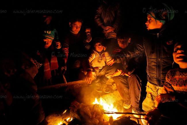Children burn trash to provide heat next to the line of people waiting outside a bakery in the Shaar neighborhood of Aleppo. This fire is the only light that glow at night in this opposition neighborhood - electricity was cut ten days ago leaving people without the means to heat their homes as the temperatures drop in the early days of December.<br /> <br /> It was midnight when most people waiting in line lost hope and began to walk home. No benzine, no bread.<br /> <br /> 12/05/2012 - Shaar neighborhoo, Aleppo, Syria...&copy;Javier Manzano