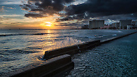 Water splashes the low breakwater wall in Waikiki Beach at sunset on O'ahu.