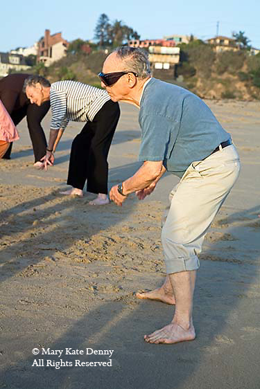 Mature male exercising with senior citizens in movement class at sunset on the beach in Playa del Rey,Los Angeles, California