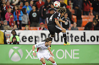 Washington, D.C.- March 29, 2014. Nick DeLeon (14) of D.C. United head the ball against Chris Tierney (8) of the New England Revolution. D.C. United defeated the New England Revolution 2-0 during a Major League Soccer Match for the 2014 season at RFK Stadium.