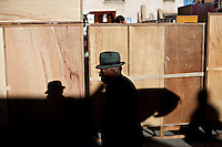 .Old man walking early morning in the 16 de Julio Street Fair.Just 25 years ago it was a small group of houses around La Paz  airport, at an altitude of 12,000 feet. Now El Alto city  has  nearly one million people, surpassing even the capital of Bolivia, and it is the city of Latin America that grew faster ...It is also a paradigmatic city of the troubles  and traumas of the country. There got refugee thousands of miners that lost  their jobs in 90 ¥s after the privatization and closure of many mines. The peasants expelled by the lack of land or low prices for their production. Also many who did not want to live in regions where coca  growers and the Army  faced with violence...In short, anyone who did not have anything at all and was looking for a place to survive ended up in El Alto...Today is an amazing city. Not only for its size. Also by showing how its inhabitants,the poorest of the poor in one of the poorest countries in Latin America, managed to get into society, to get some economic development, to replace their firs  cardboard houses with  new ones made with bricks ,  to trace its streets,  to raise their clubs, churches and schools for their children...Better or worse, some have managed to become a sort of middle class, a section of the society that sociologists call  emerging sectors. Many, maybe  most of them, remain for statistics as  poor. But clearly  all of them have the feeling they got  for their children a better life than the one they had to face themselves .