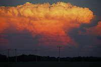The tell-tale anvil cloud of a severe thunderstorm is illuminated a golden-orange by the setting sun along the Texas/Oklahoma border in late September. Such Cumulonimbus clouds are harbingers of extremely large hail, high winds, heavy rains and sometimes tornadoes.