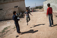 In this Sunday, Sep. 29, 2013 photo, ABDU EL KADER, a Syrian child plays football with his brothers and neighbours outside his family house in Madaya village after attended classes in the public school in the Idlib province countryside of Syria. Children have come back to school in the rebel controlled territory despite the constant threaten of shelling and the ongoing fighting, and public schools still operating financially under the Syrian government administration. (AP Photo)