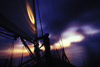 Trimming the sails by penlight aboard sailing yacht 'Heron', after sunset at sea in French Polynesia