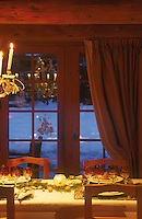 The dining table is laid for dinner with a decoration of spruce and nuts down the centre