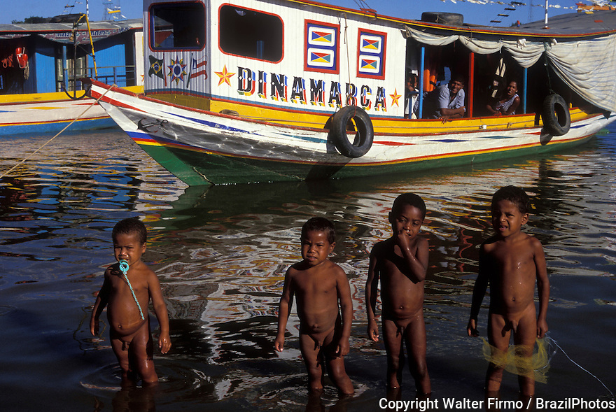 Four black children play in the waters of Sao Francisco river, at Bom Jesus da Lapa city, Bahia State, Brazil. Five-years old boys, naked boys, typical boats of Sao Francisco river, Northeastern Brazil, South America, Latin America, four children, 4 children, children´s play.