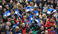 Bath fans in the crowd wave flags in support. LV= Cup match, between Bath Rugby and Exeter Chiefs on November 17, 2013 at the Recreation Ground in Bath, England. Photo by: Patrick Khachfe / Onside Images
