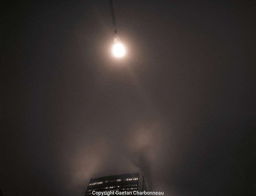 A lampost and the top of a building under a foggy night